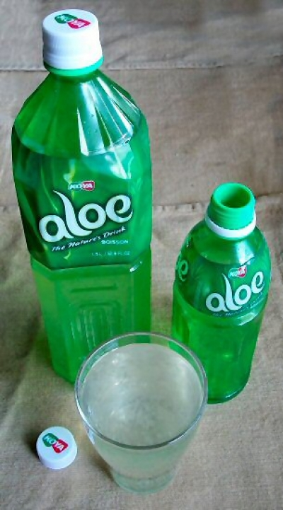 Aloe Vera beverage in large and small bottles, and a glass of the product showing the natural plant pulp: healthier than soda pop at least