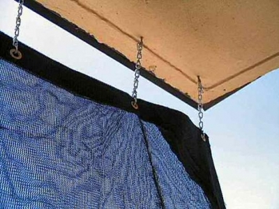 the nylon weave tarpaulin eye-hooks attached by short lengths of chain to the patio ceiling