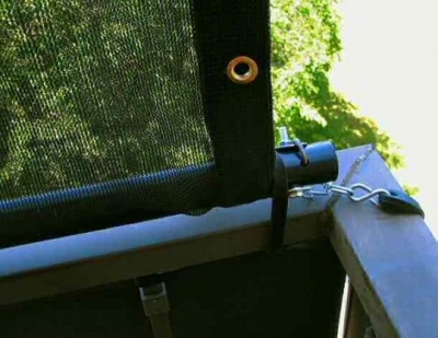 close-up view of how the tarpaulin and PVC pipe attach to the balcony rail with rubber bungy straps