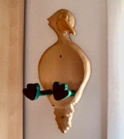 woodworking project: a towel holder in the shape of a duck sitting with legs extended outward