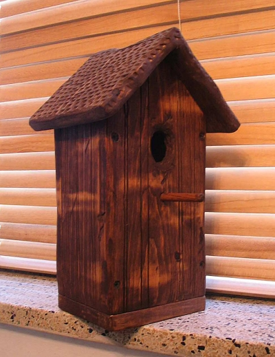 Finished birdhouse, stained and ready for a family of birds to move in