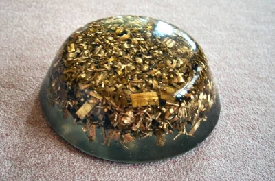 An Orgonite 'Tower Buster' that is made with brass shavings, embedded quartz crystals and clear Epoxy Resin