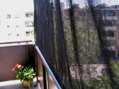 weave-mesh tarpaulin view as attached to PVC pipe in the bottom, tied to balcony rail with rubber bungy cords