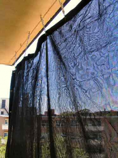 mesh-weave tarpaulin hanging from eye-hooks creates an excellent sun-shade for the balcony patio