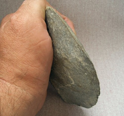 the simple stone-ax as it would be held, useful for striking the ground to dig-up roots and insects